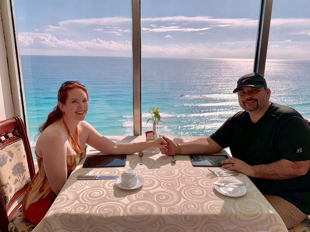 couple holding hands at breakfast in front of an oceanview windo