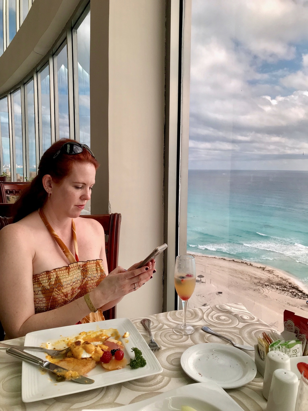 woman looking at menu at table at oceanfront restaurant