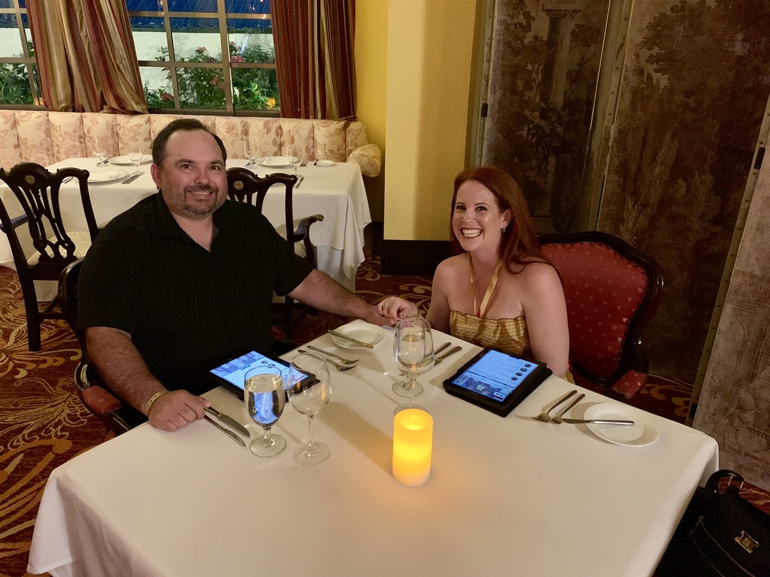 man and woman holding hands at dinner table