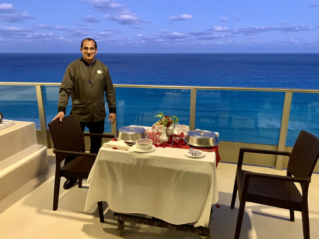 server at table on balcony with ocean view