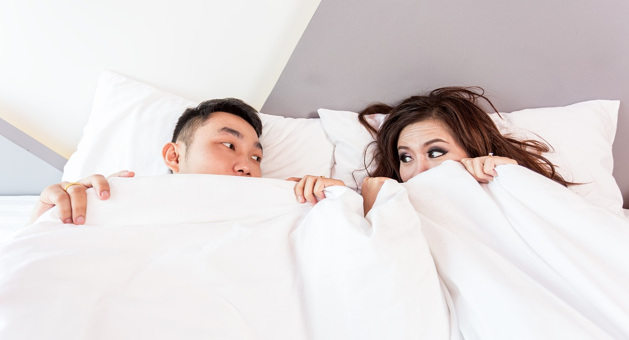 Man and woman in bed under covers