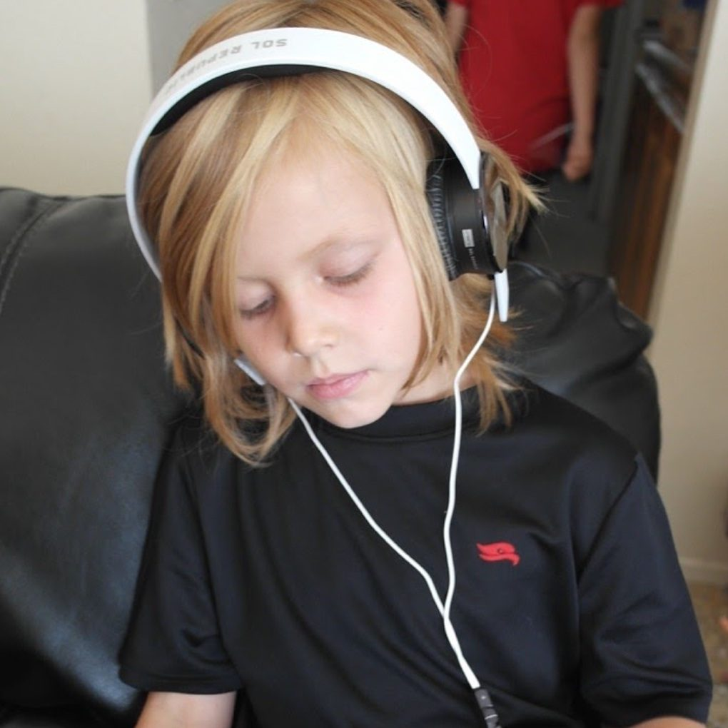 young boy listening to music with headphones on phone