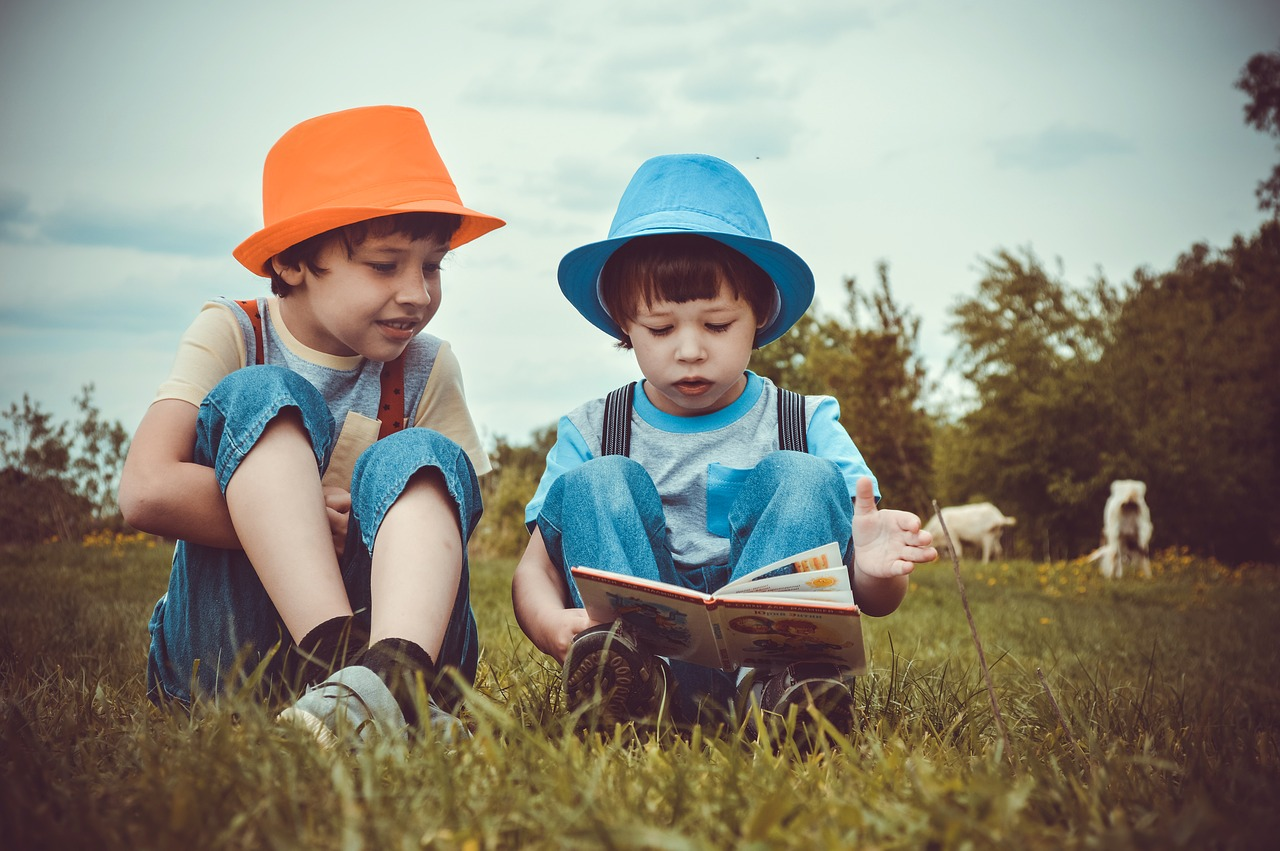 Boys reading a book in the grass