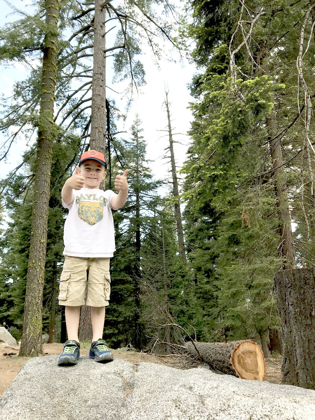 boy standing on rock with two thumbs up