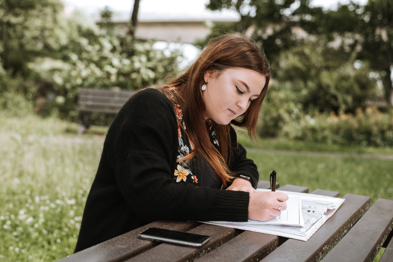 Woman Writing Essay on Table Outside