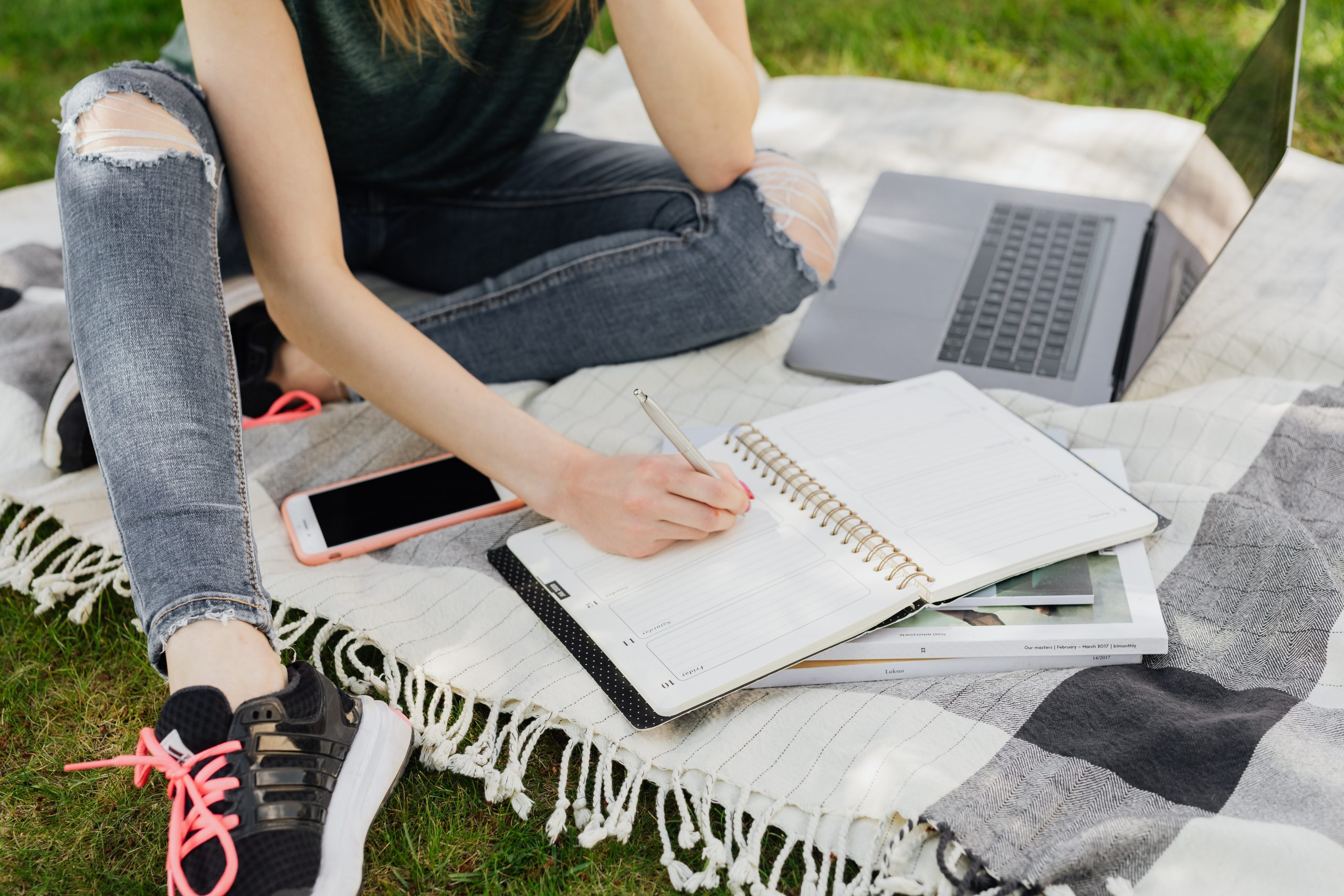 girl with laptop and notepad on blanket in grass