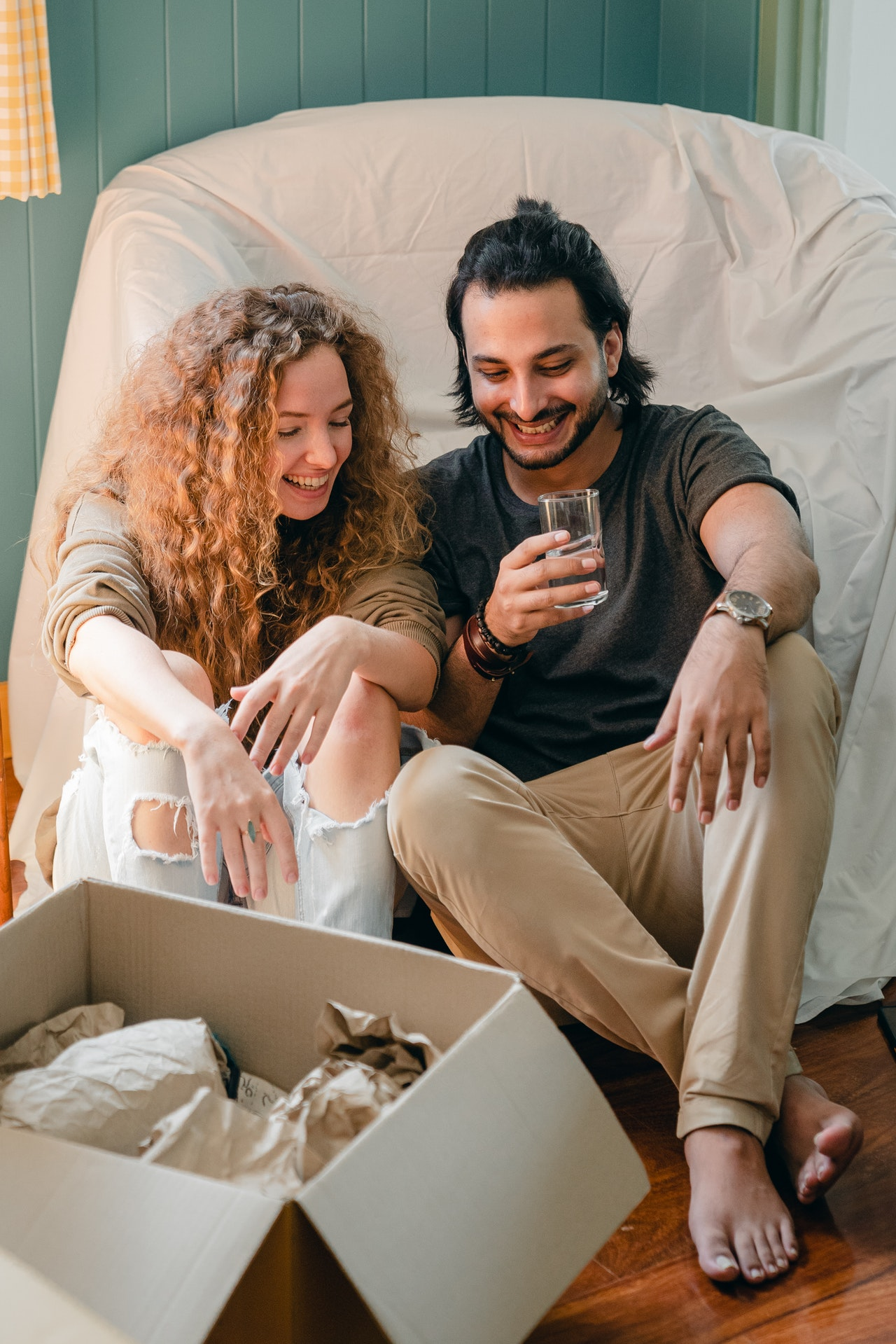 couple Drinking over packed boxes from moving