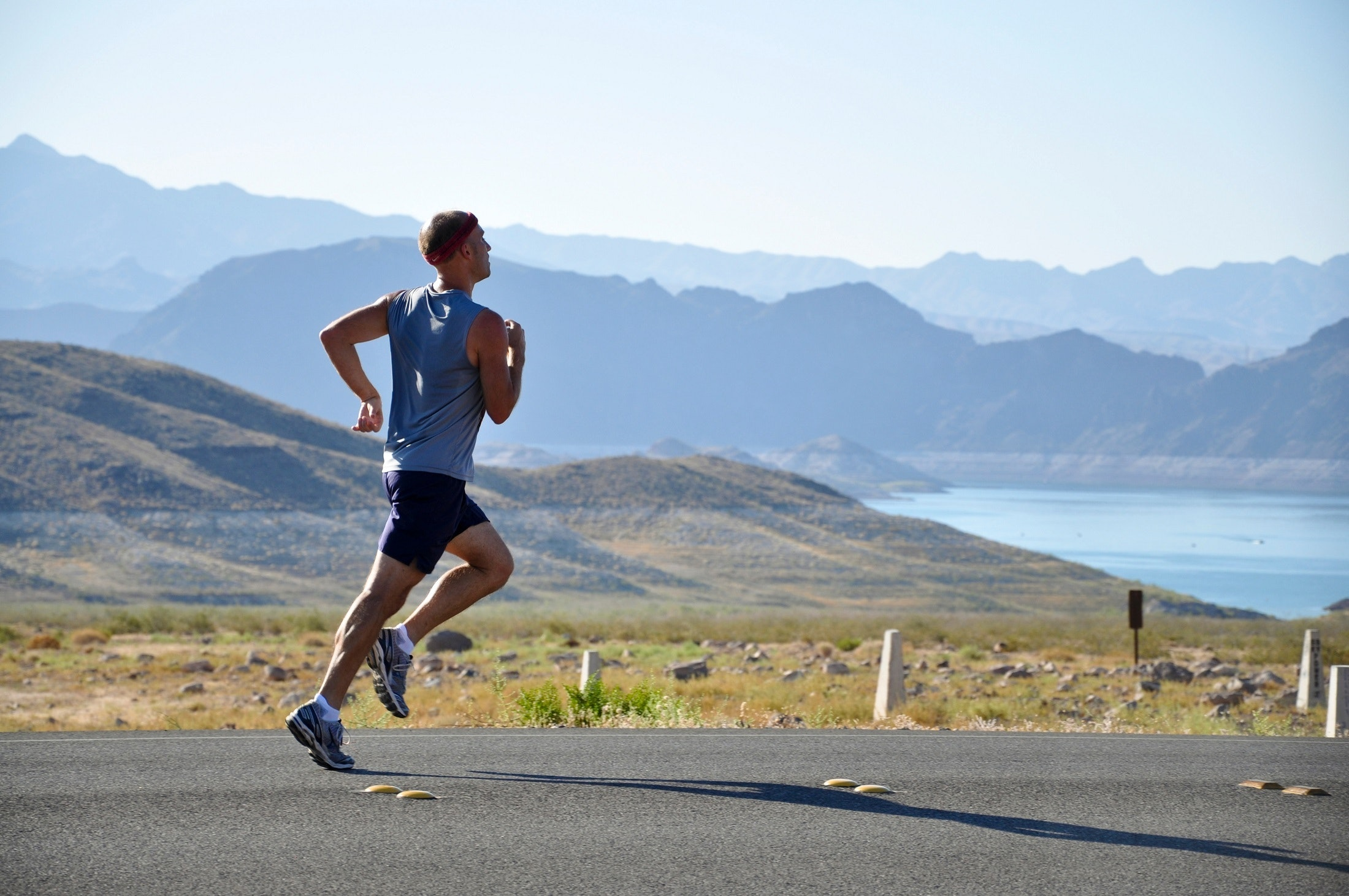 Man running on road by lake and mountains