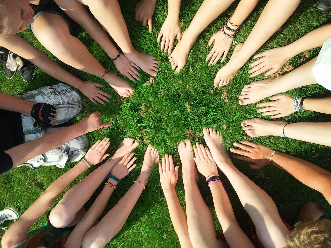 hands feet in grass