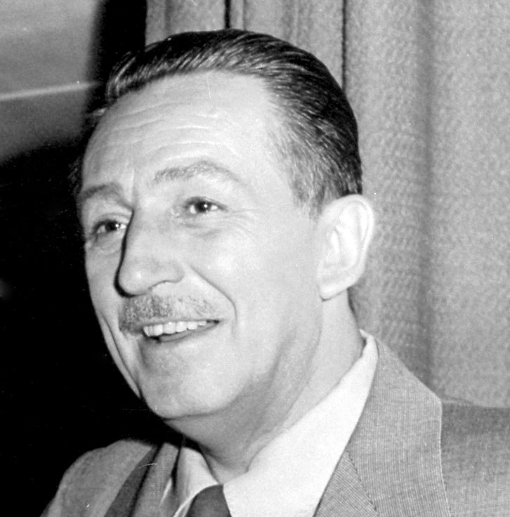 Walt Disney wearing a suit and tie smiling at the camera
